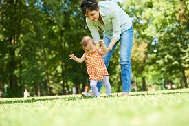 stock photo of mother baby nature  - happy mother and baby child in park making first steps  - JPG