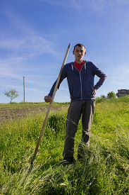 stock photo of scythe  - outdoors in green grass boy standing holding scythe - JPG