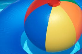 stock photo of pool ball  - Water fun with a Floating tire and Beach Ball in the paddling pool - JPG