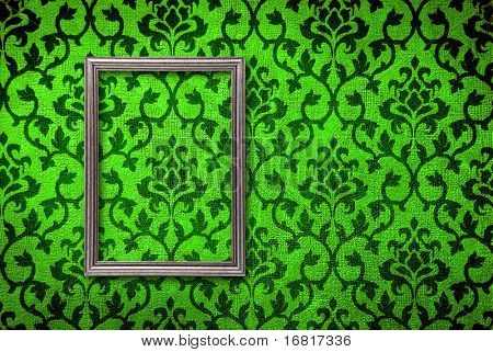 Silver frame on a vintage green wall background