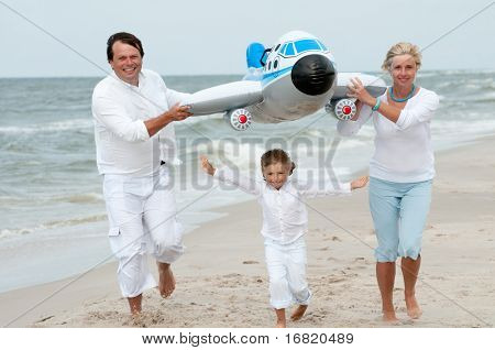 Travel - happy family playing at the beach (no-name inflatable toy)