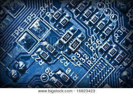 close up of electronic circuit blue background
