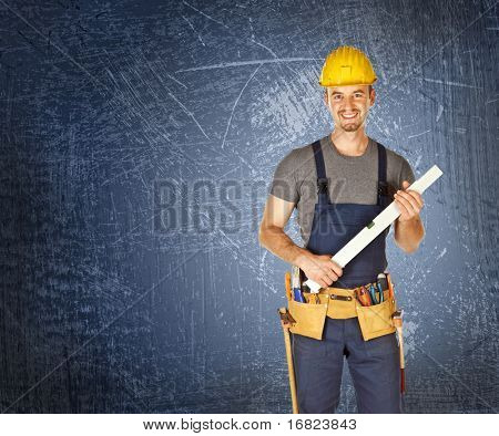 smiling manual worker standing and holding spirit level
