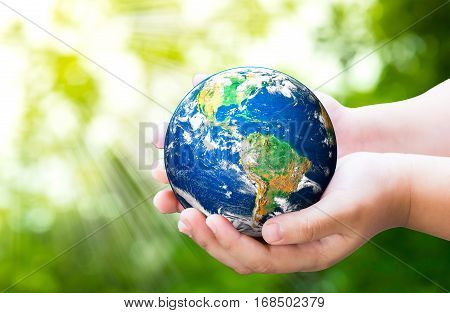 Planet in child hands on against green spring background. World Environment Day. World Mental Health Day concept.