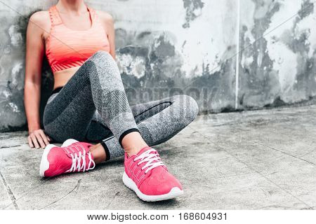 Fitness sport woman in fashion sportswear doing yoga fitness exercise in the city street over gray c