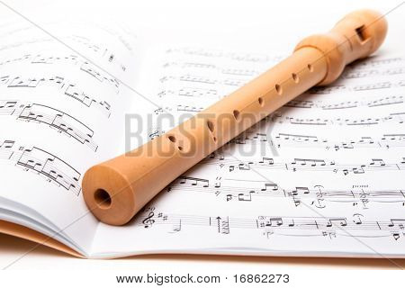 Wooden flute on sheet music. Close up.