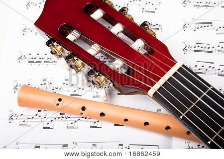 Guitar and wooden flute on sheet music. Close up.