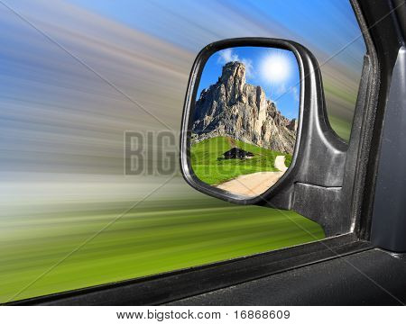 Rear view mirror reflecting beautiful mountain scenery