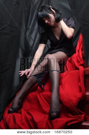 Low key studio shot of slim stripping girl in black nylons on red background