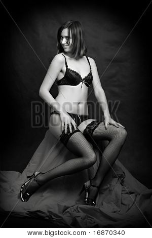 Low key lighting studio shot young attractive women in black sexy lingerie - monochrome studio shot