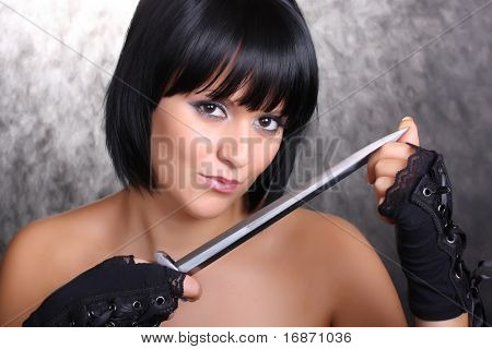 Beautiful girl with a dagger on a black background. Great for calendar.