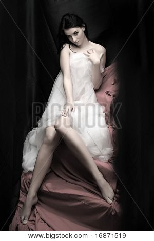 Beautiful slenderness young woman in bridal veil on pink background. Low key studio shot. Great for calendar.