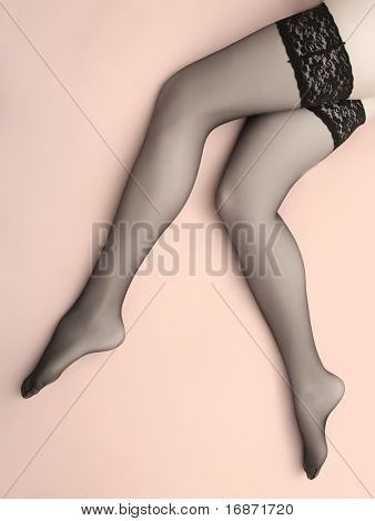 Studio shot beautiful slim legs in black nylons on a pink background. Great image for calendar.
