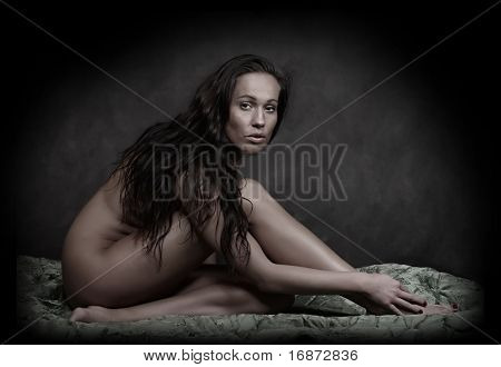 Classical artistic nudity style picture of woman sitting on green brocade background. Great for calendar.