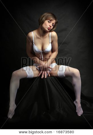 Flirty girl with long slim legs in white nylons. Vintage style low key photography. Great for calendar