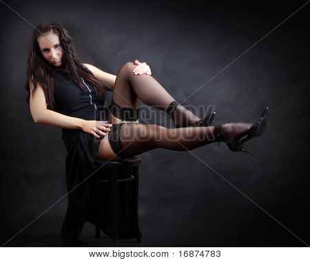Sitting flirty girl with long slim legs in black nylons. Vintage style low key photography. Great for calendar.