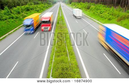 Motion blurred trucks on highway.