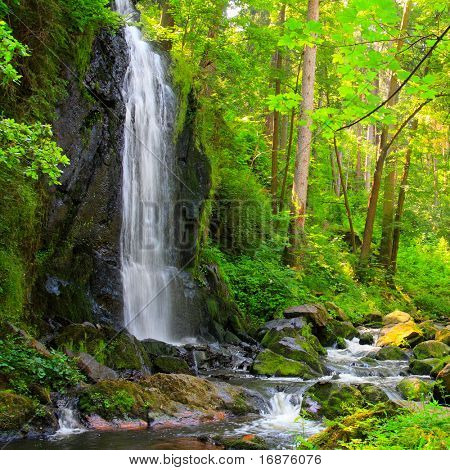 Beautiful waterfall in green forest. Scenery from Novohradske Hory - mountains in Czech Republic - Europe