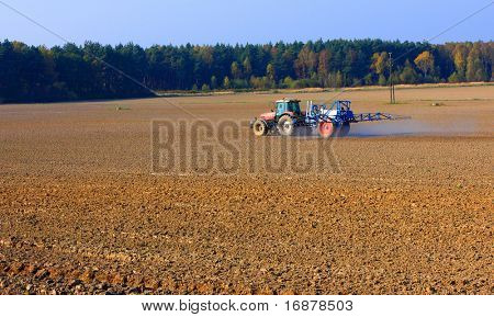 The tractor fertilizing field in autumny day