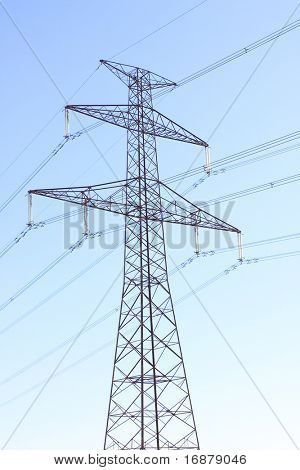 High voltage power tower and electrical lines against blue sky.