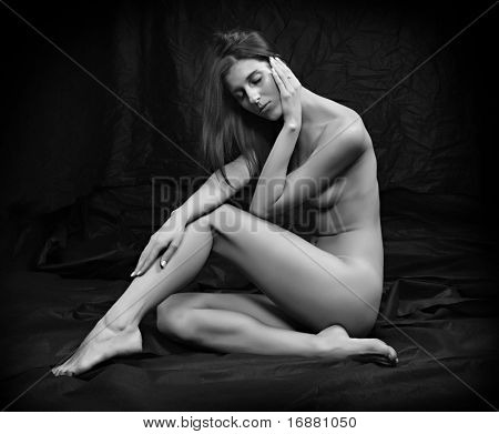 Monochrome photography of sad woman sitting on black background.