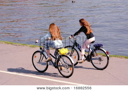 two young girls are riding the bicycles at the river