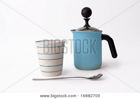 cup of cappuccino, long spoon and coffee kettle