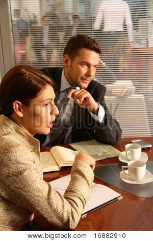 Business man and woman sitting at the desk in the office and having meeting