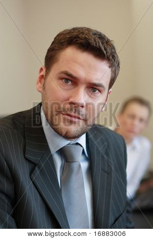 35 years old standing business man portrait - woman out of focus in background