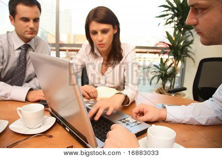 Group of business people sitting at the table, working with laptop, 2 men and 1 woman