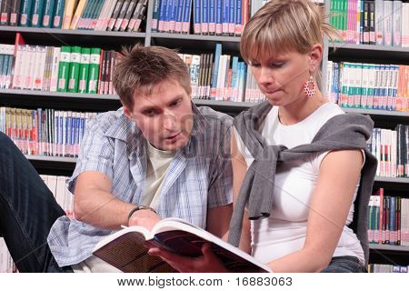 man and woman reading book in the library