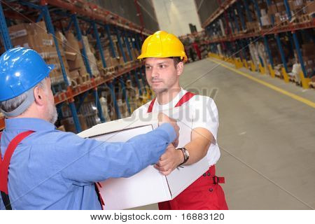 one worker in uniform receiving box from another  in warehouse