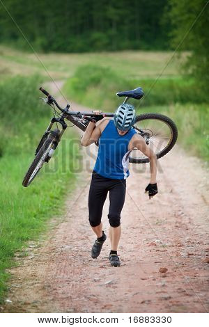 Running competitor cyclist  carrying bicycle