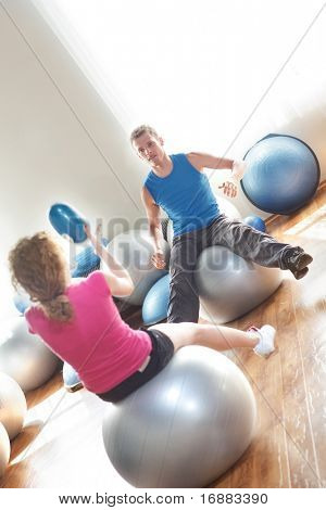 Man and woman working out with balls