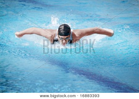 Swimmer in cap breathing performing the butterfly stroke