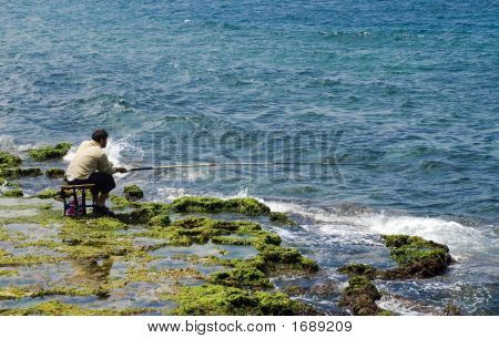 Fishermen Sitting  And Fishing  On The Rock Coast Near The Sea