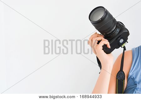 Woman holding a professional DSLR camera above her shoulder suggesting her being a professional photographer