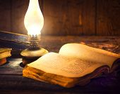 Old oil lamp and old books in darkness. Vintage kerosene lantern and open old book with blank pages  poster