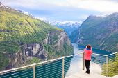 Tourist Looking At Geirangerfjord From Flydasjuvet Viewpoint Norway poster