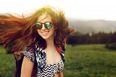 Stylish Woman Traveler With Fashionable Sunglasses And Windy Hair Smiling And Having Fun On Top Of M poster