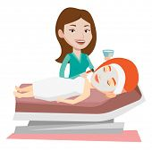 Cosmetologist applying cosmetic mask on face of female client in beauty salon. Woman lying on table  poster