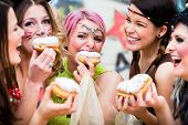 Girls at German Fasching Carnival eating doughnut-like traditional pastry poster