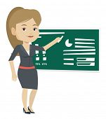 Young teacher standing in classroom. Teacher standing in front of blackboard with piece of chalk in  poster