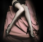 stock photo of slender legs  - Beautiful slim legs in black nylons on a pink background - JPG