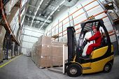 stock photo of forklift  - forklift  truck reloading pallets in storehouse - JPG