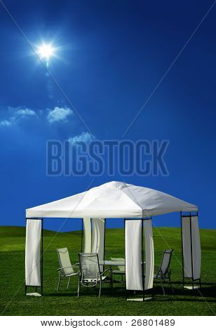 chairs and table under white picnic tent on green grass