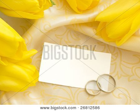 blank paper note with wedding rings and yellow tulips