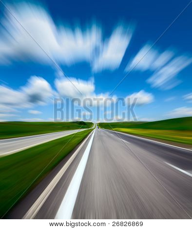 motion blurred road and cloudy blue sky