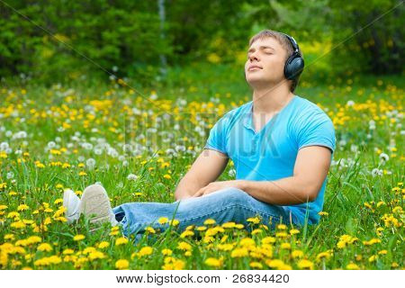 Portrait of a relaxed young man sitting on grass in park and listening to music on headphone