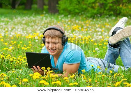 Cheerful young man working with a laptop and listening music on headphone outdoors